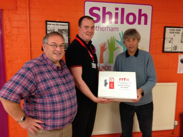 Mike Smith of Rapid Relief Team handing over parcel to Managers John and Jonathan.