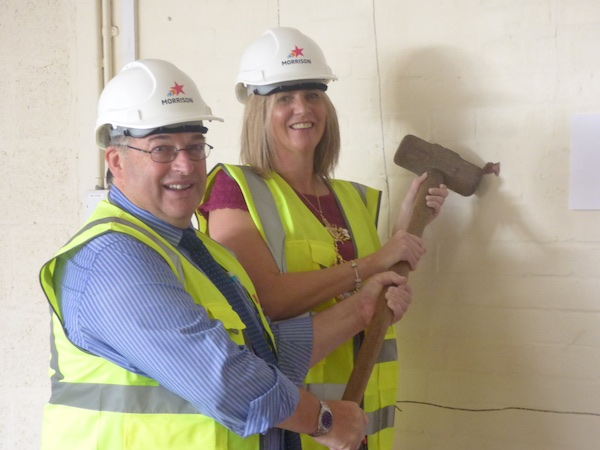 Madam Mayor, Lyndsay  Pitchley 'hits the first brick' to create the servicing hatch with Shiloh's Manager, John McDonnell providing a little support
